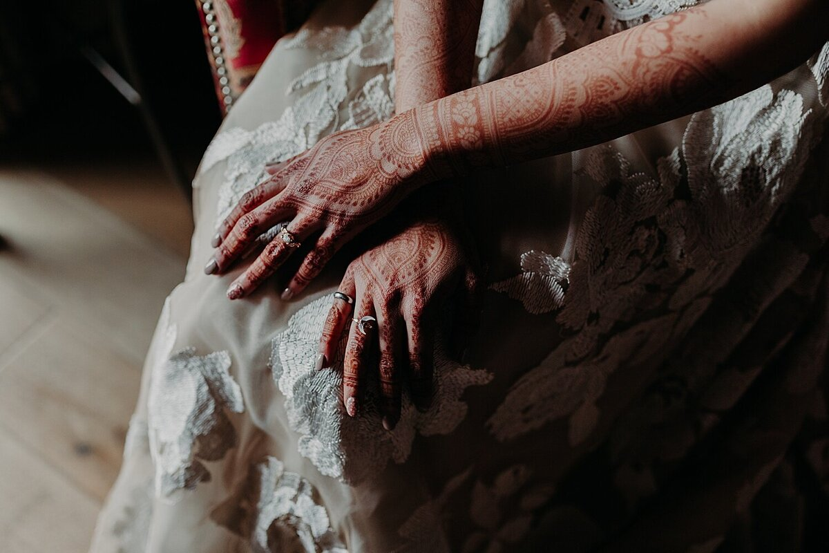 Bride with Henna on her arms and hands sits in a white wedding dress and overlaps her hands