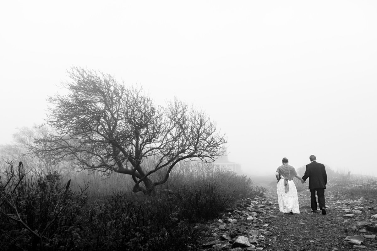 The couple walk along the rocky shore by the Seacoast Science Center in Rye NH after eloping on a foggy day