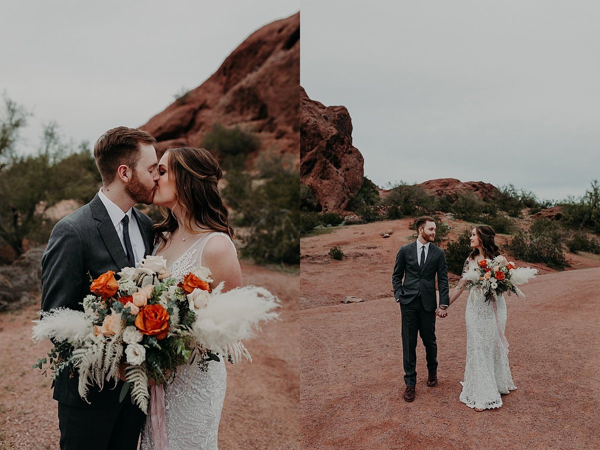 bride and groom walk through the desert and red rocks while holding bouquet