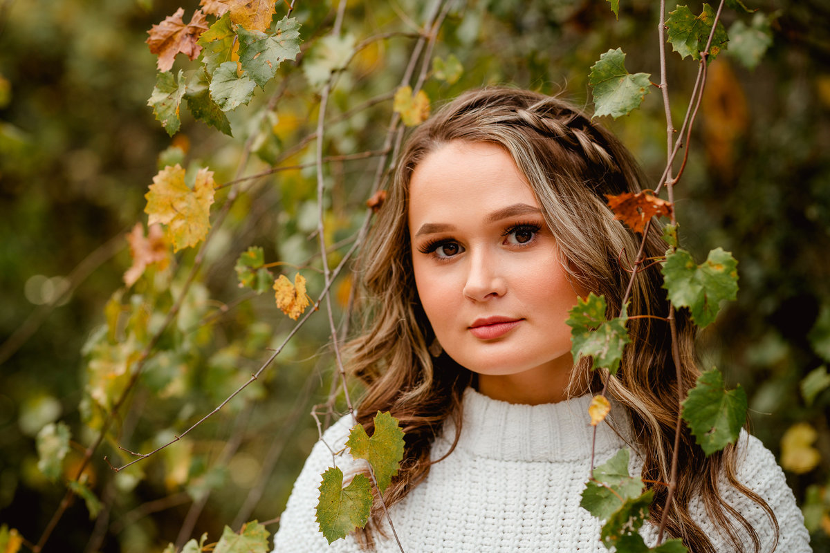 Close up portrait photo of high school senior with fall leaves in Florida.