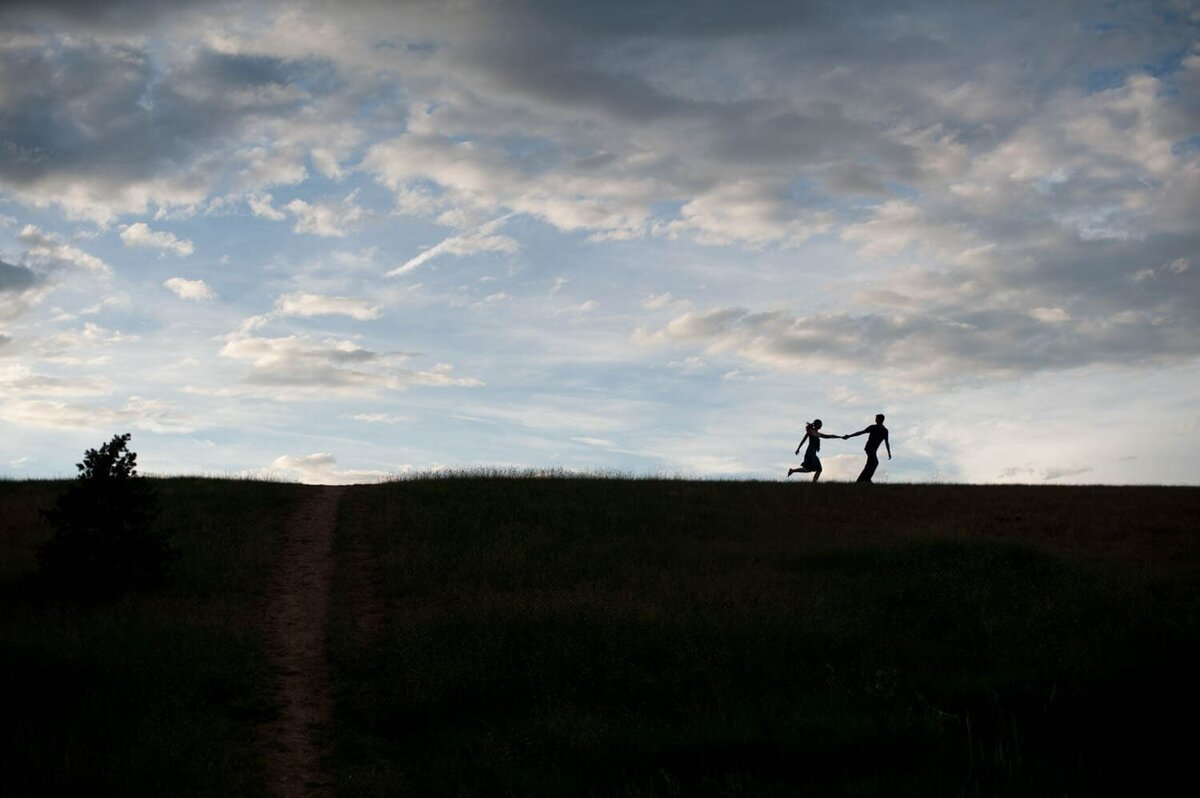 a silhouette on a tall hill with pretty clouds of a man pulling a woman along behind