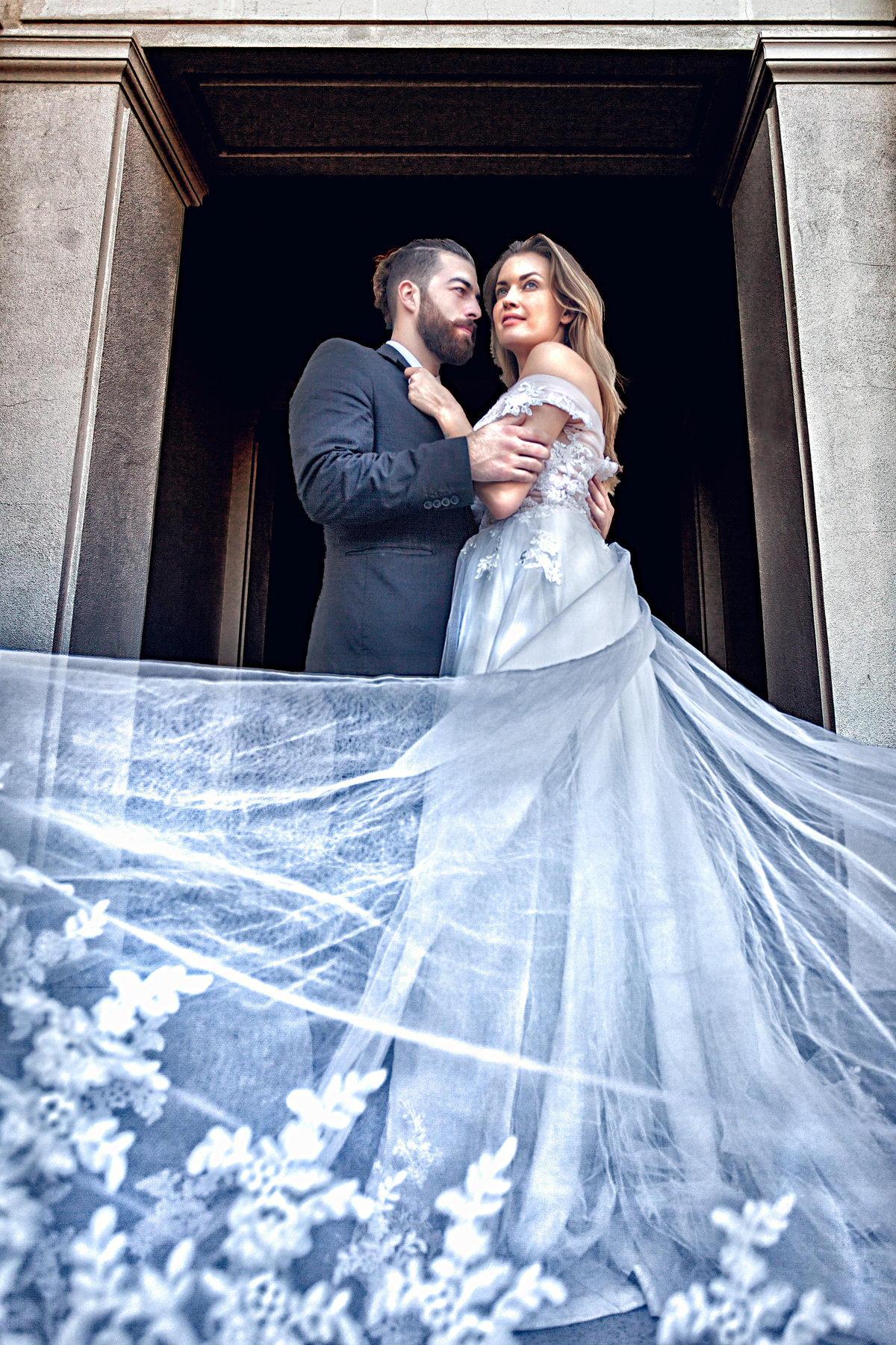 A bride and groom look at each other in the archway of a townhall, while the wedding dress flows towards the viewers eye, dramatically lighting the wedding dress.