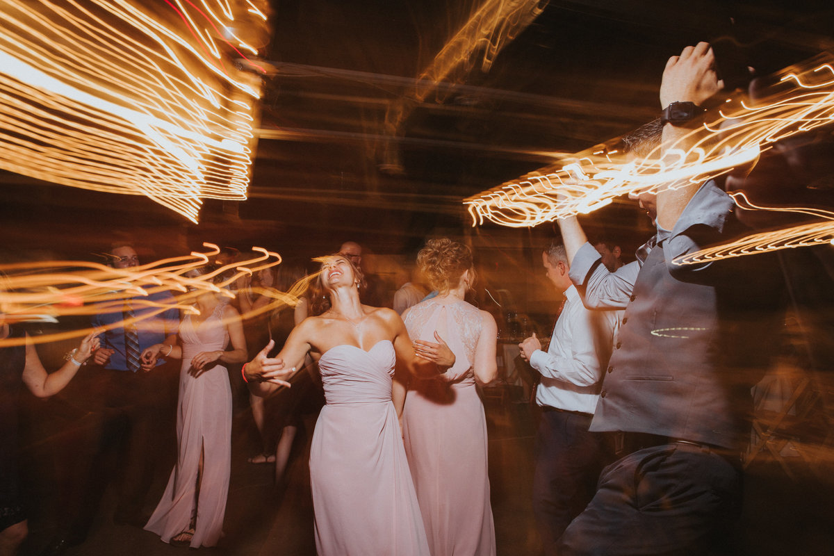 A bridesmaid dancing the the live band at a wedding reception