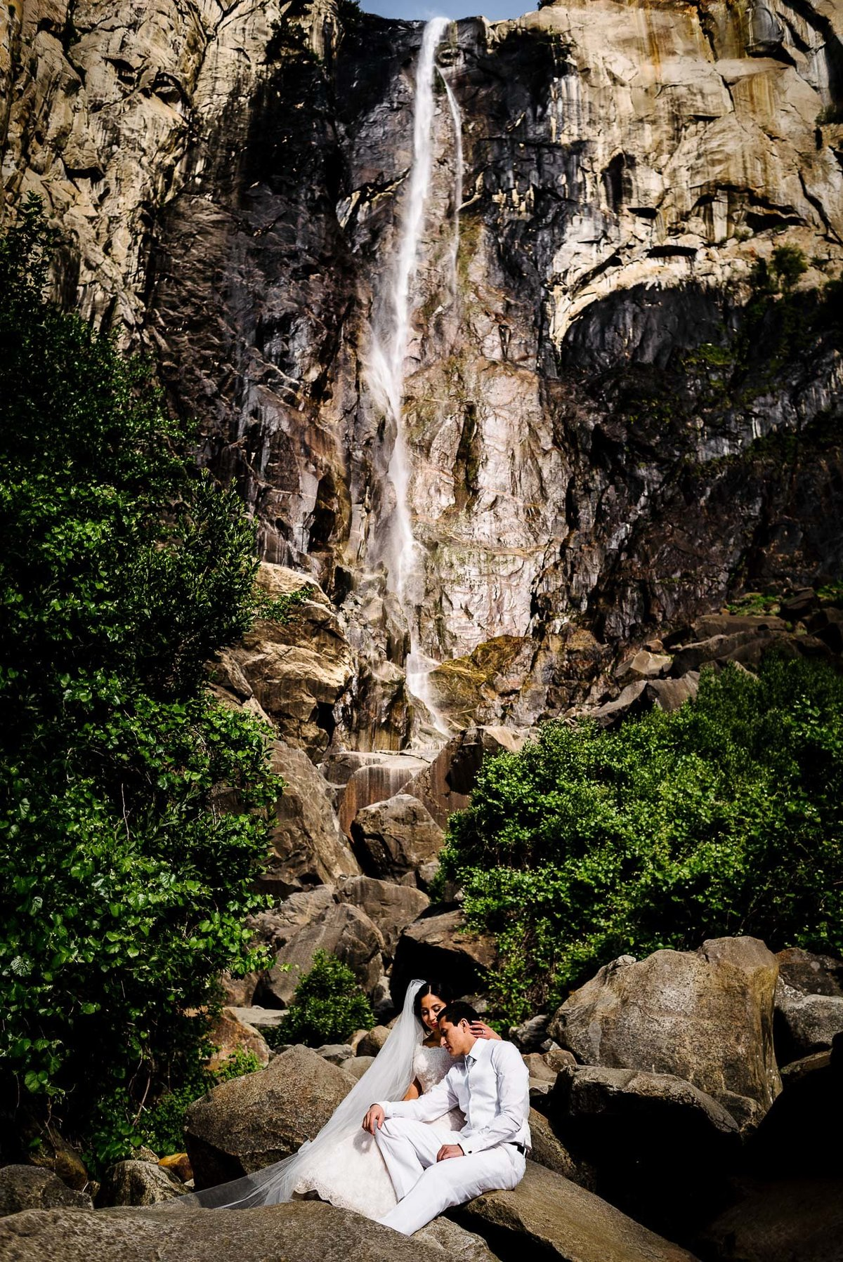 bridal portrait in front of bridal waterfall  aT YOSEMITE NATIONAL PARK