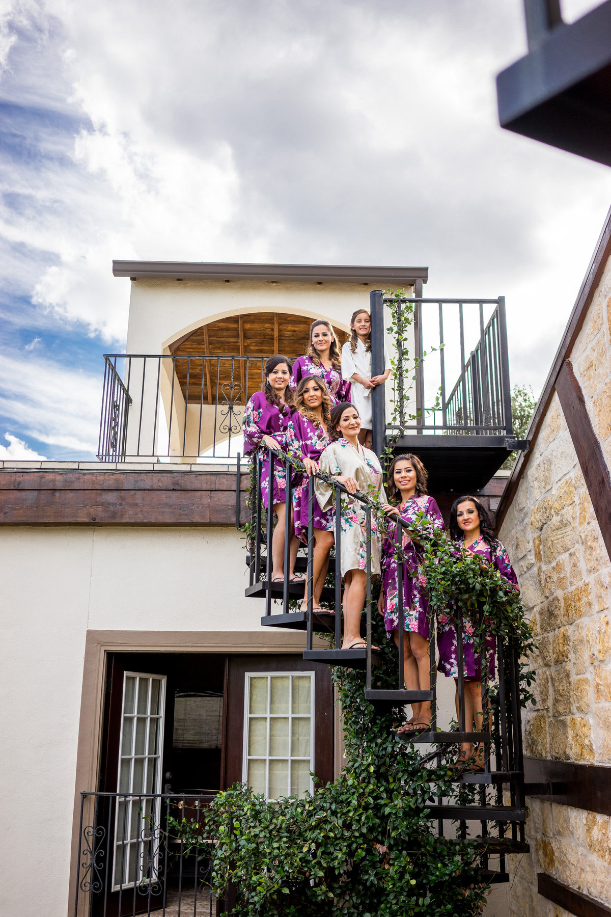 bridesmaids and bride standing on spiral stair case while getting ready for wedding ceremony at Marquardt Ranch venue