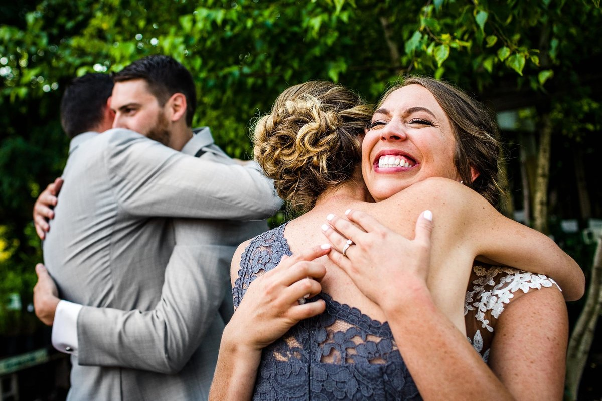 Guests hug each other during a Blumen Gardens wedding ceremony.