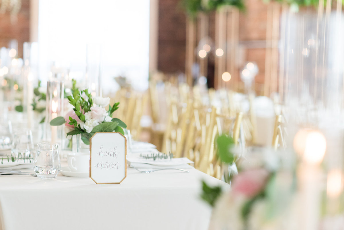 Custom calligraphy table names by Amy Sylvia Designs sits atop a flower and candle laden table at The Chanterelle