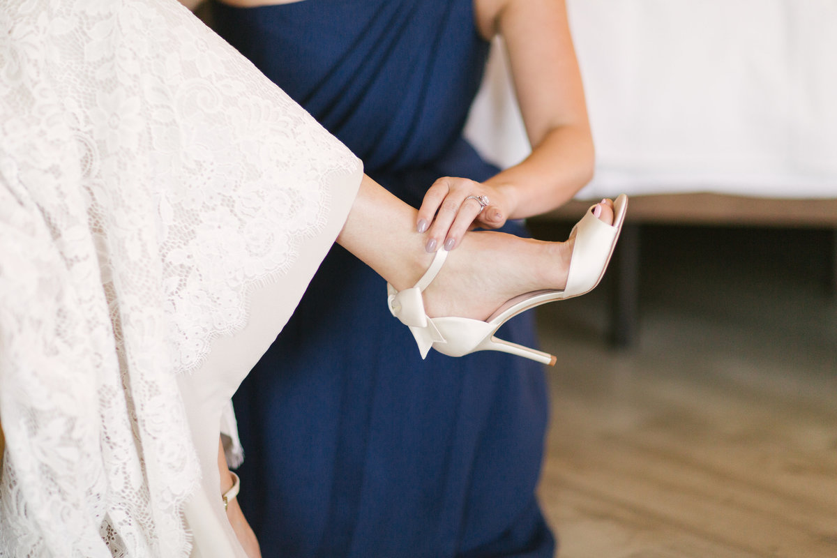 Bridesmaid helps bride put on shoes prior to wedding at Firestone Vineyard