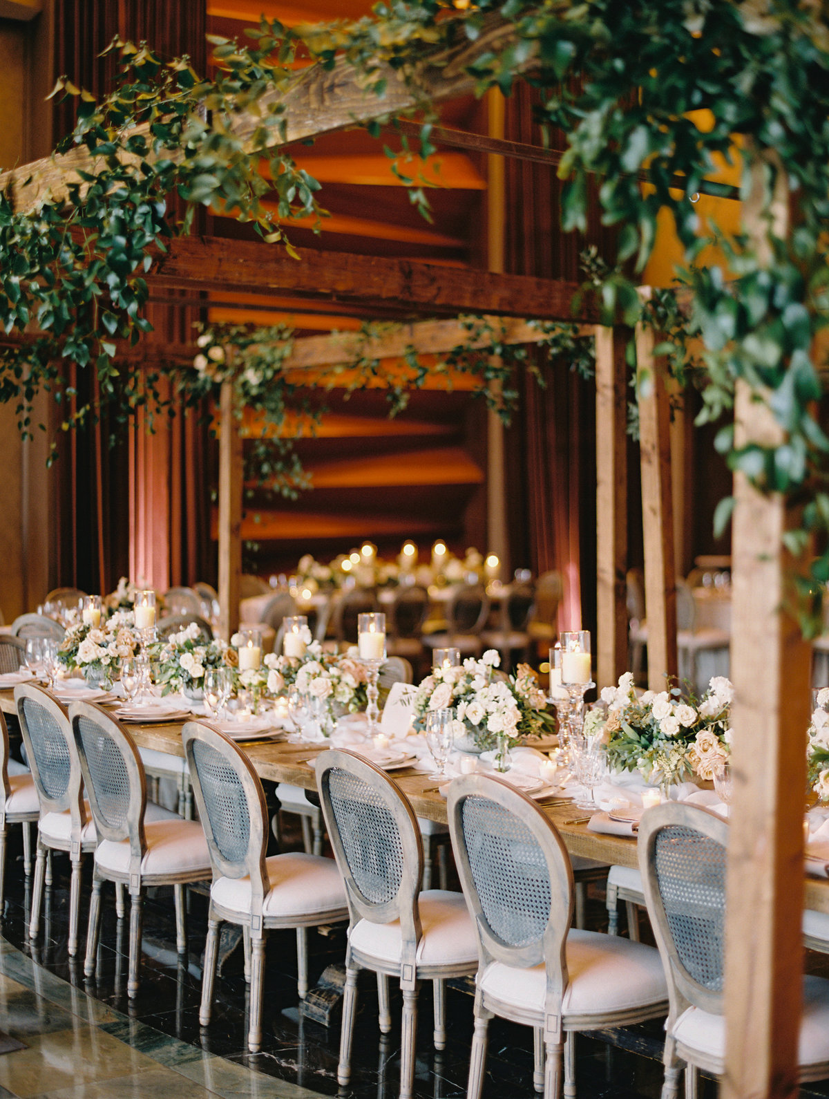 a picture of a wedding at Red Rock Casino in Las Vegas with rustic wood cabanas and a long rustic tablescape with cane back chairs and a beautiful lush flower centerpiece