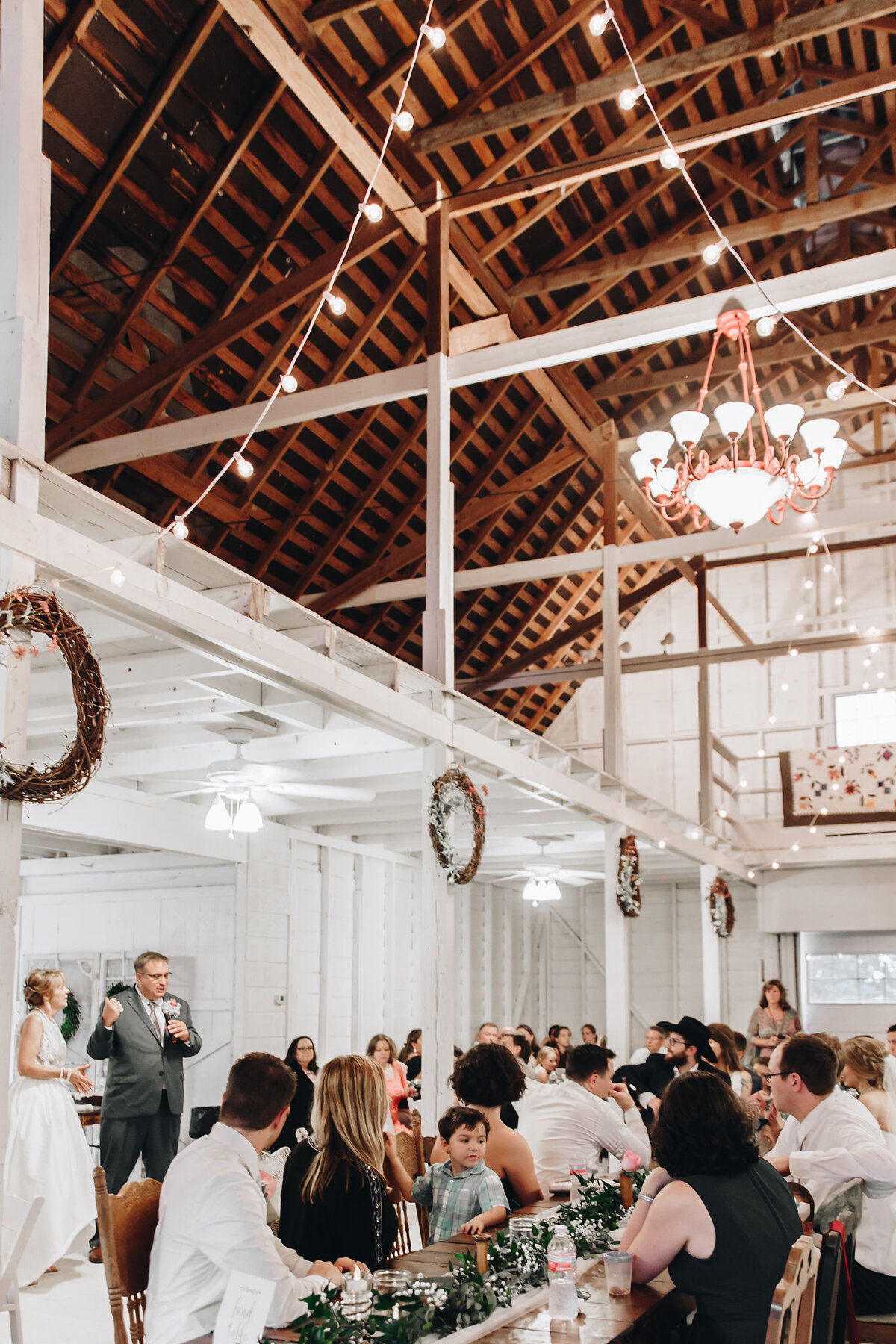 The Grand Texana's Reception hall. A gorgeous dairy barn transformed into a reception hall. The photo shows guests attending the reception, string lights hanging from the ceiling and the bride and groom are giving a speech