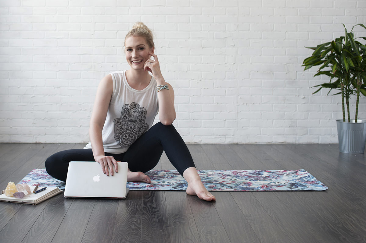 female sitting on yoga mat with a laptop