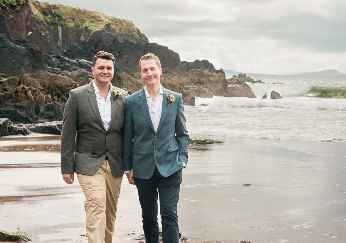 Two grooms in suits, walking on the beach together