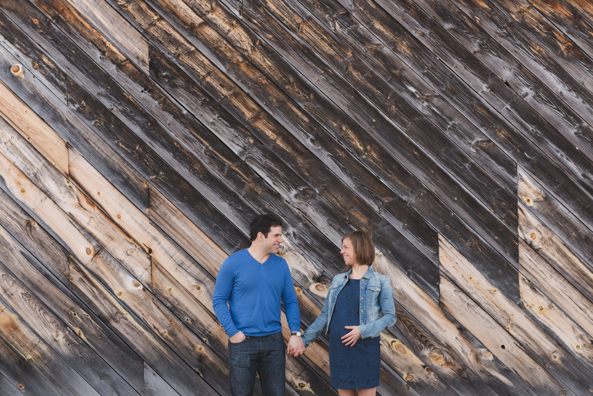 Parents to be standing in front of barn board holding hands