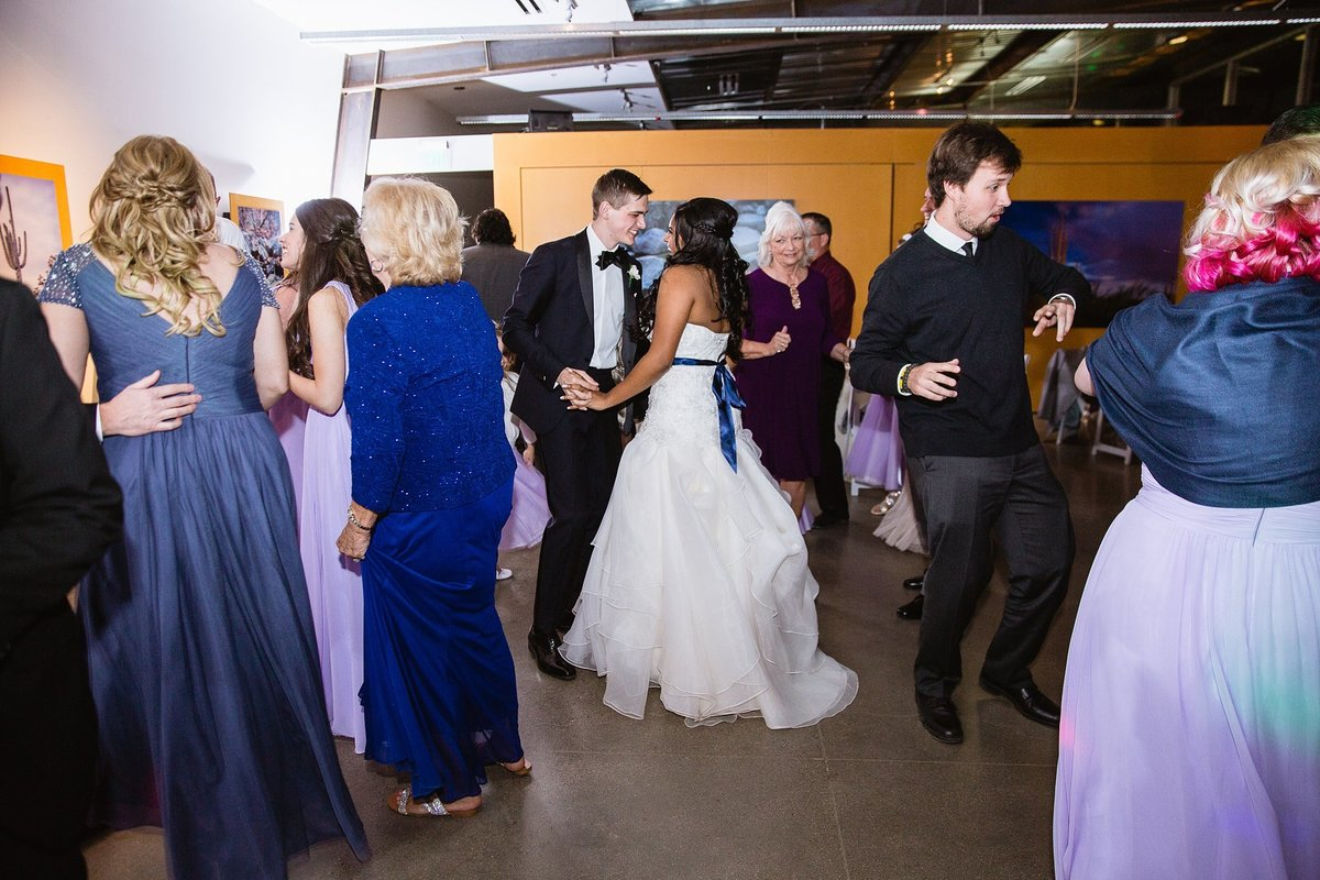 Bride and groom dancing with guests at wedding reception by Phoenix wedding photographers PMA Photography.