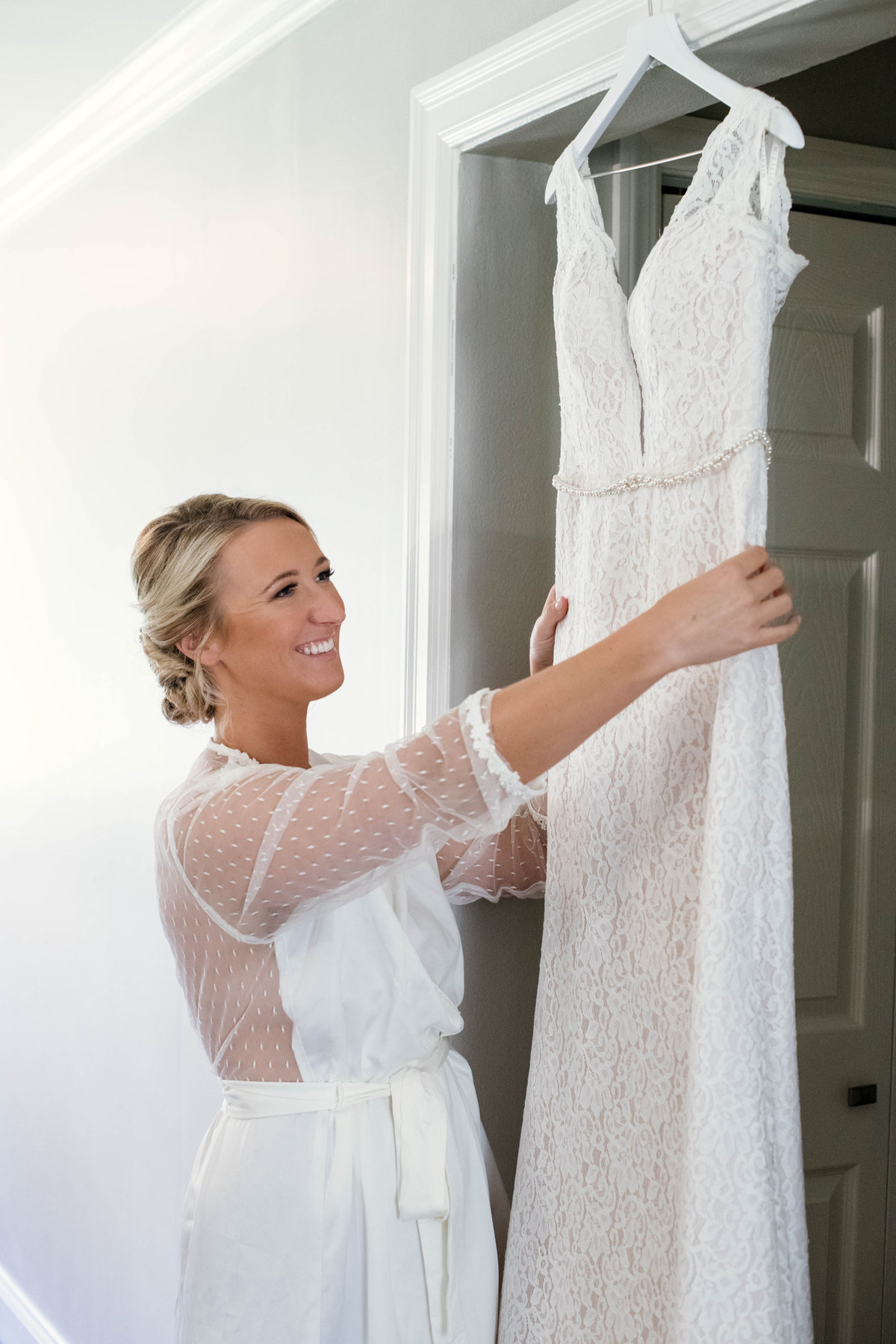bride smiling and holding her wedding dress from wedding at Mansion at Timber Point