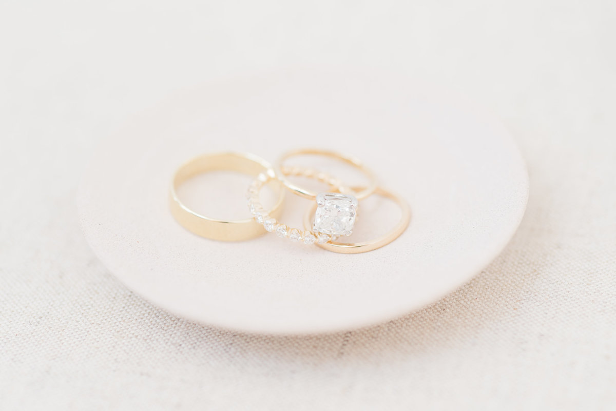 bride-and-groom-wedding-band-and-engagement-rings-styled-on-plate