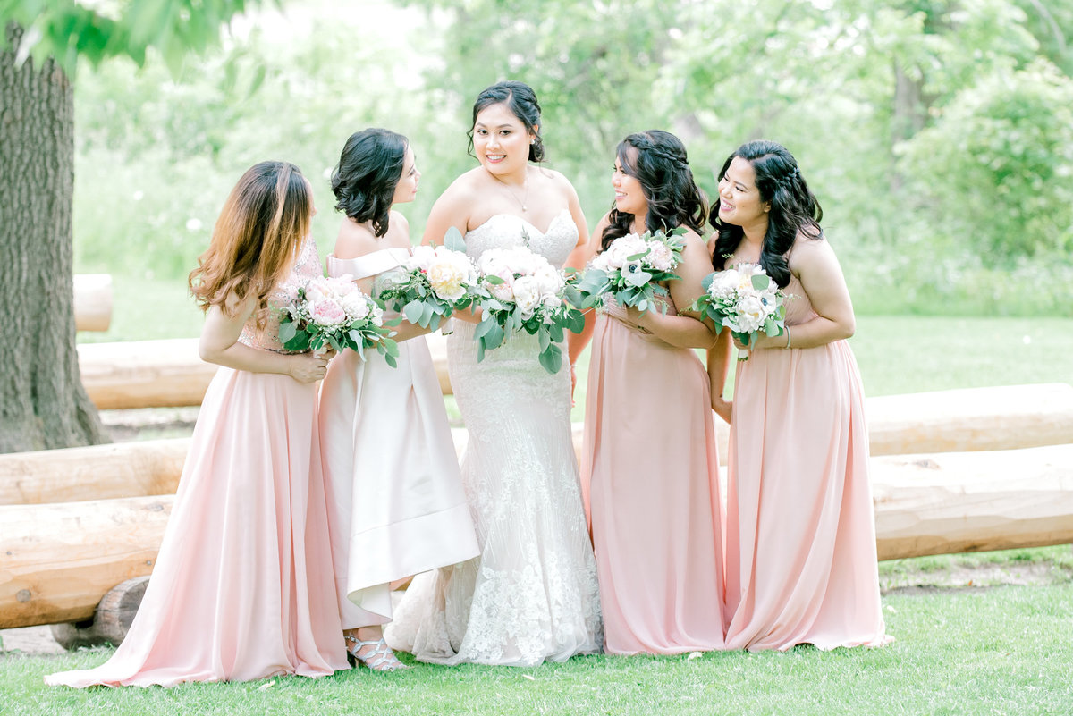 bride and bridesmaids looking at eachother laughing and holding flowers