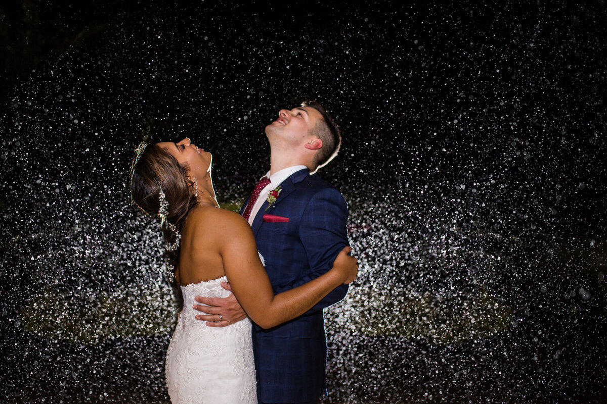 bride and groom dancing in the rain on their wedding day