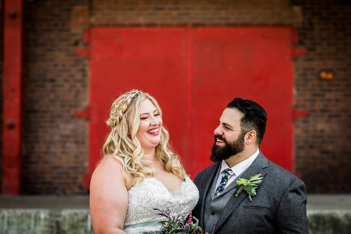 A couple laughs together in front of a red door before their Kitchen Chicago wedding.