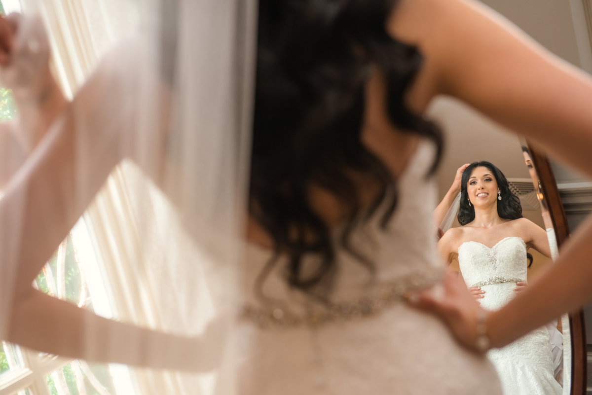 Bride putting her veil on at Glen Cove Mansion