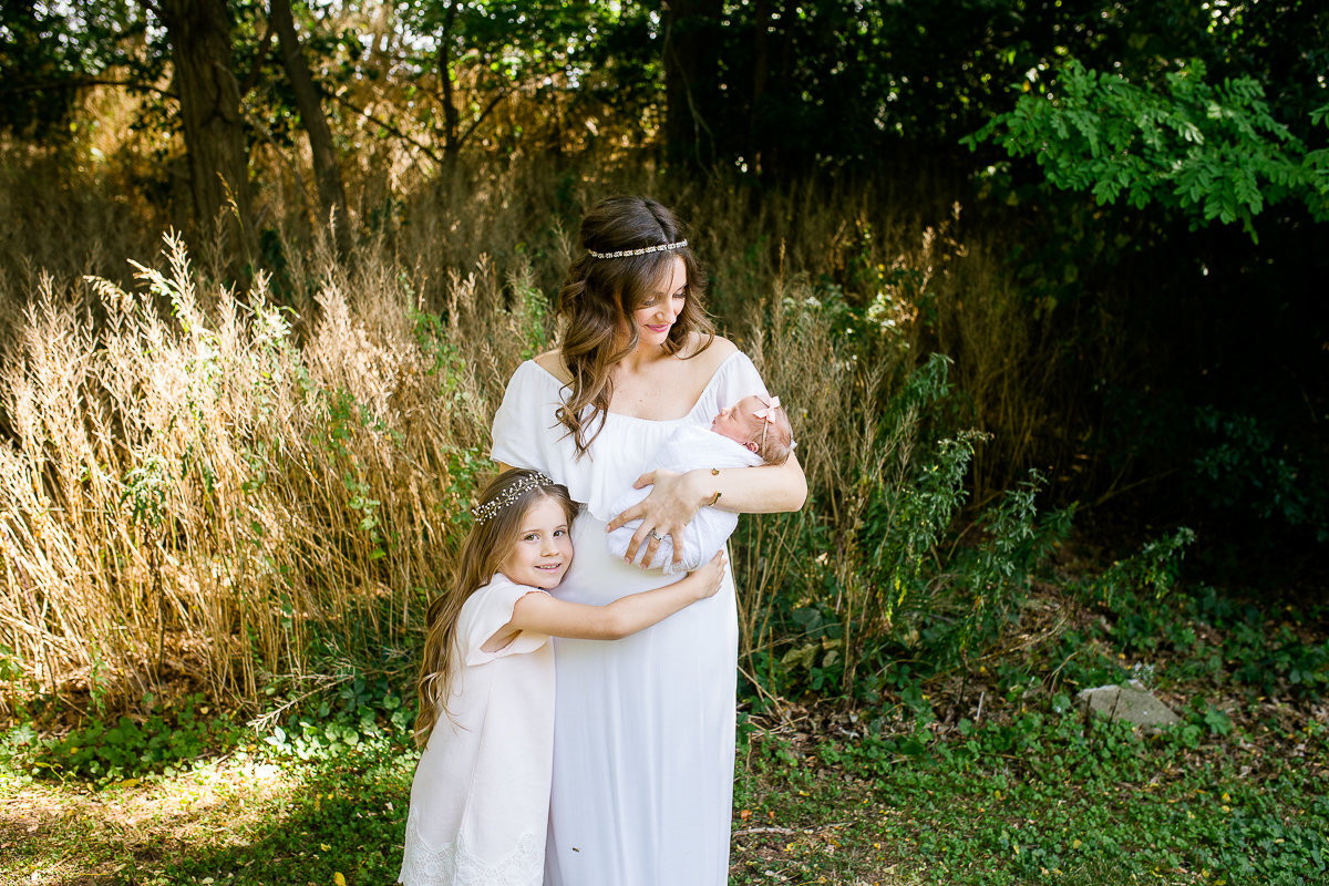 Daughter hugging mother who is holding newborn baby sister {Oakville Family Photographer}