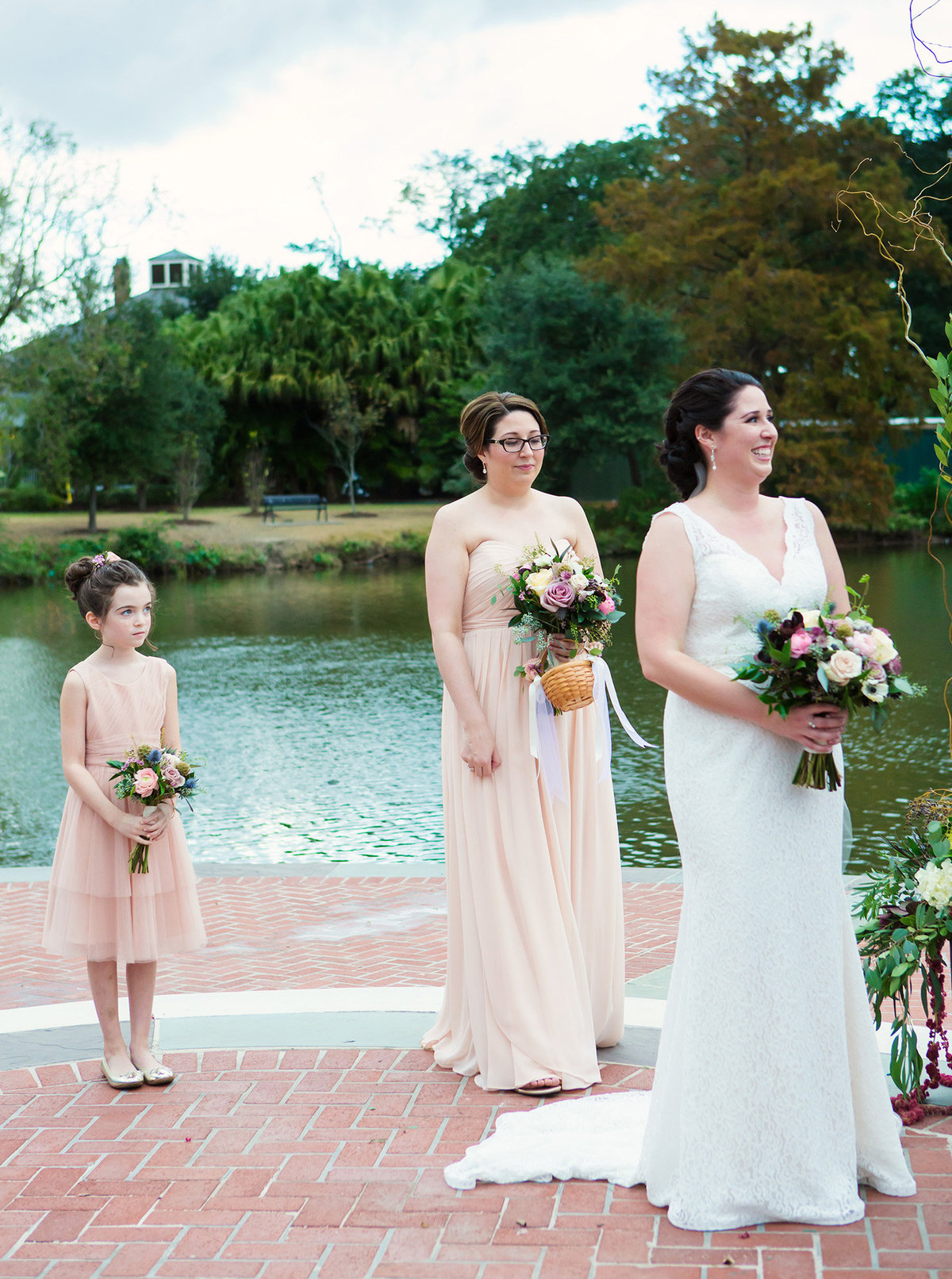 new orleans bride standing at the altar with matron of honor and flower girl beside a pond in Audubon Park