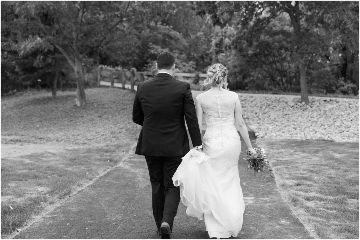 bride and groom walking down trail, black and white wedding photography