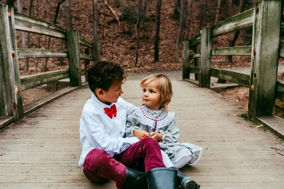 Brother and Sister sitting on wooden bridge staring at each other