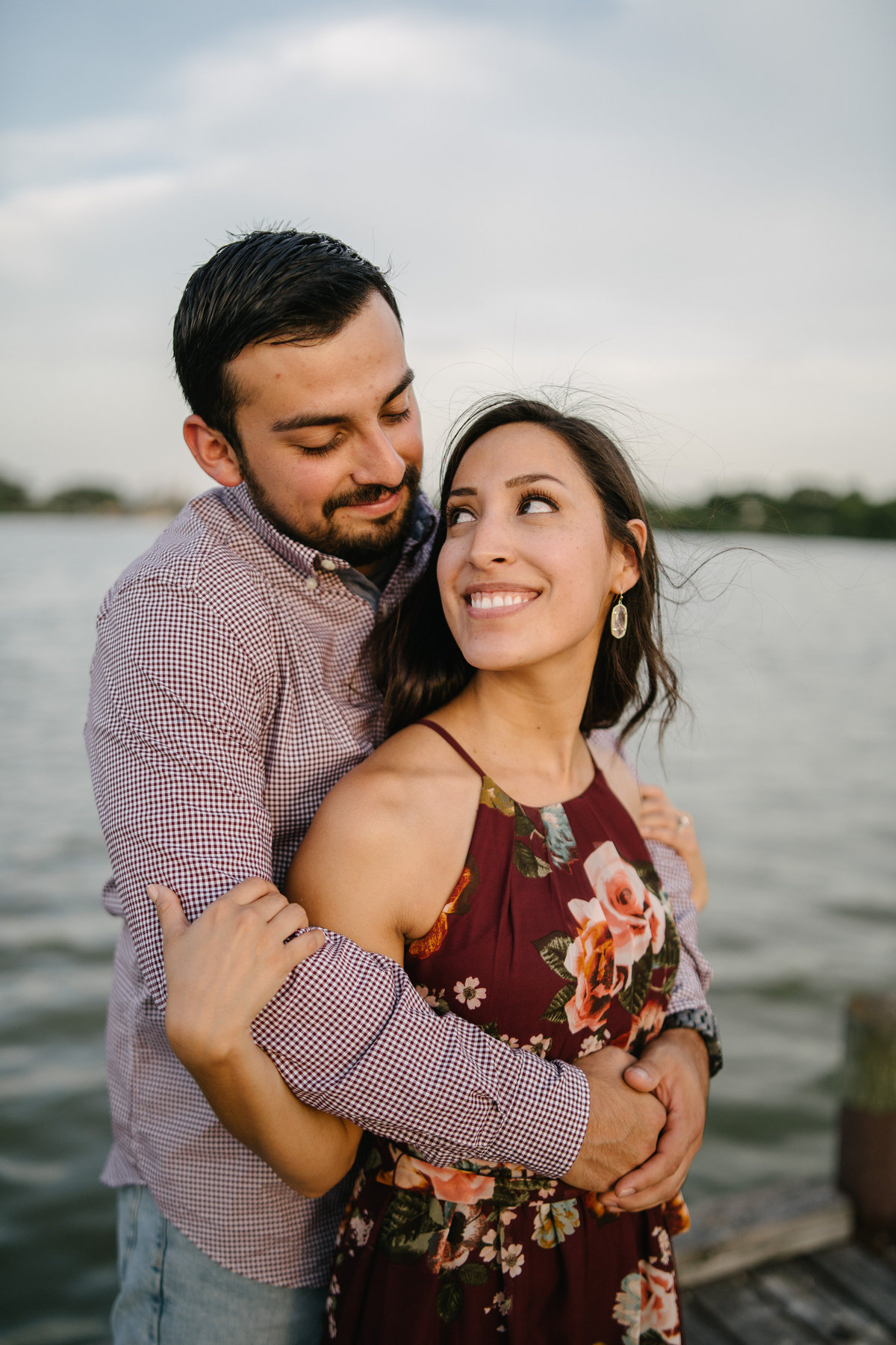 Fiancé is holding his bride to be on a wooden pier at Woodlawn Lake in San Antonio. They are engaged and soon to be married.