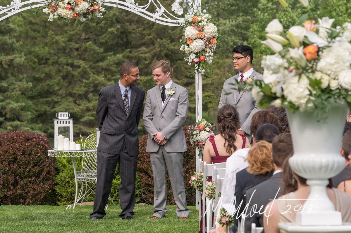 groom stands next to officiant while they wait for the bride