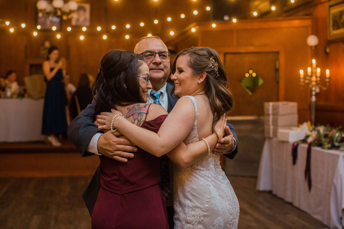father dancing with both of his daughters at wedding recetion at Union Hotel in Occidental, California