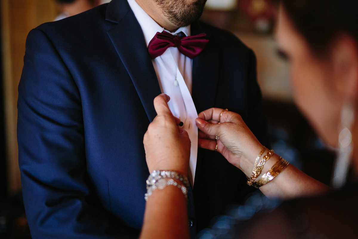 mother of groom assists groom with tie before wedding ceremony in Texas Hill Country wedding