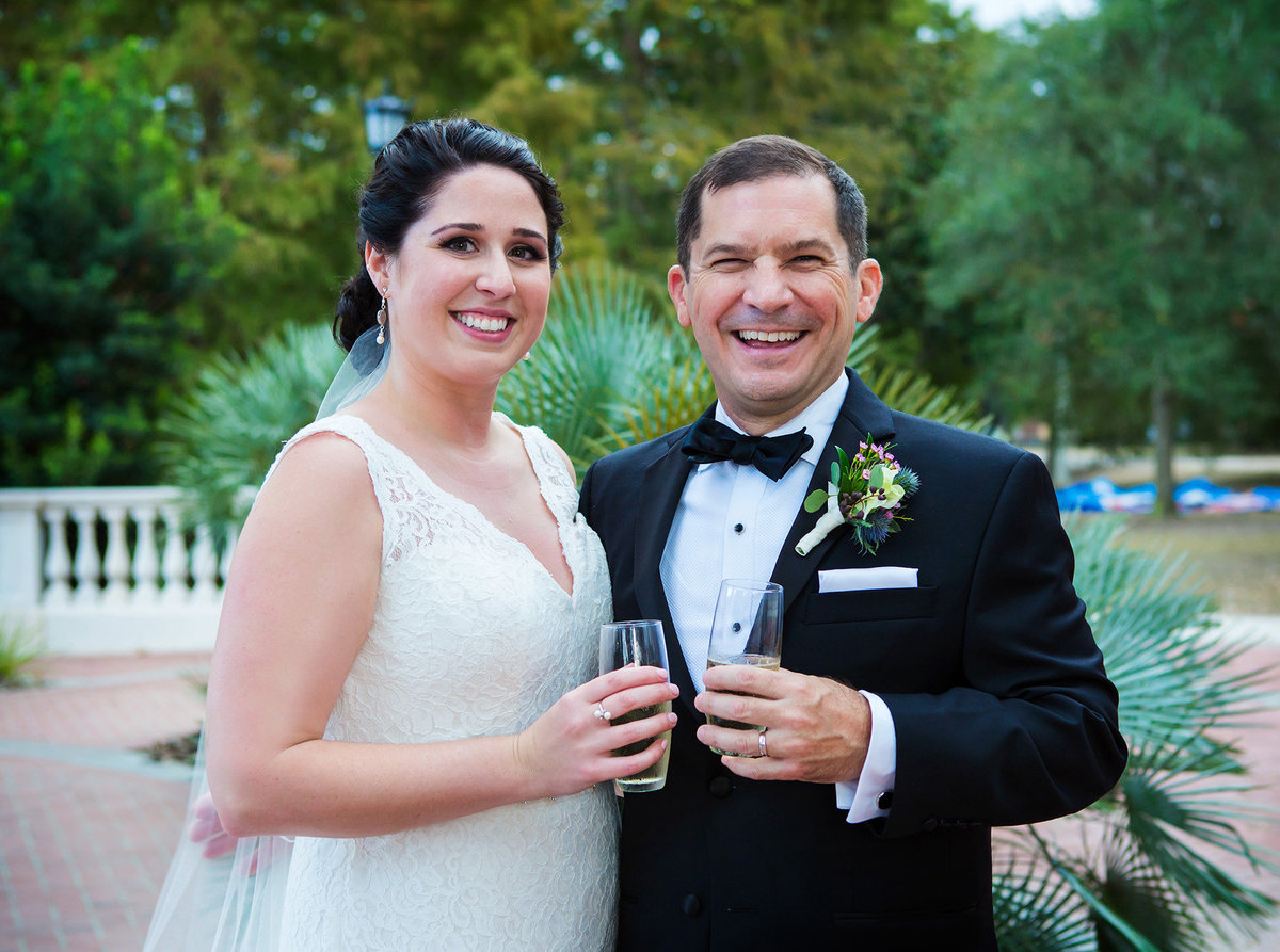 NOLA wedding couple with champagne glasses after wedding ceremony in Audubon Park