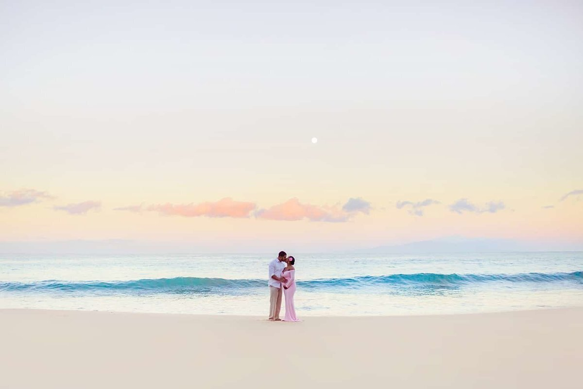 Couple kissing on the beach at sunrise with full moon setting on the horizon