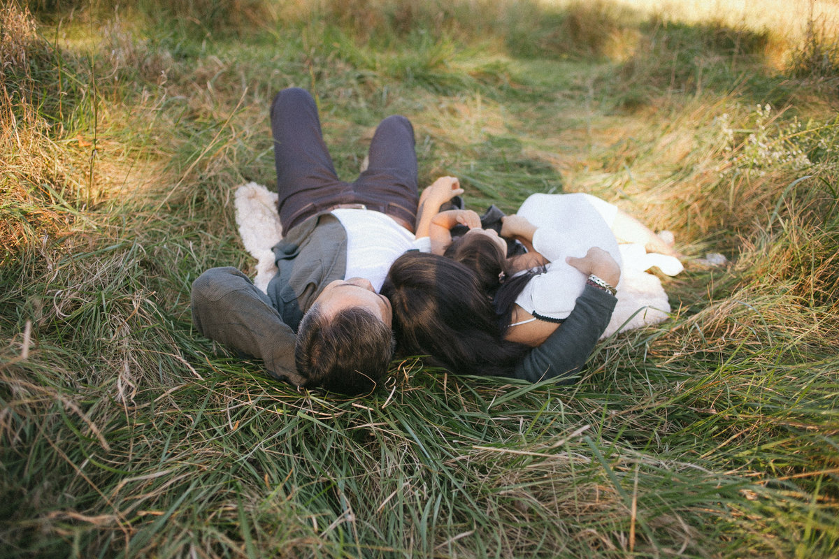 Family of three laying outdoors in long grasses in Mokena Illinois, photo by Elle Baker Photography
