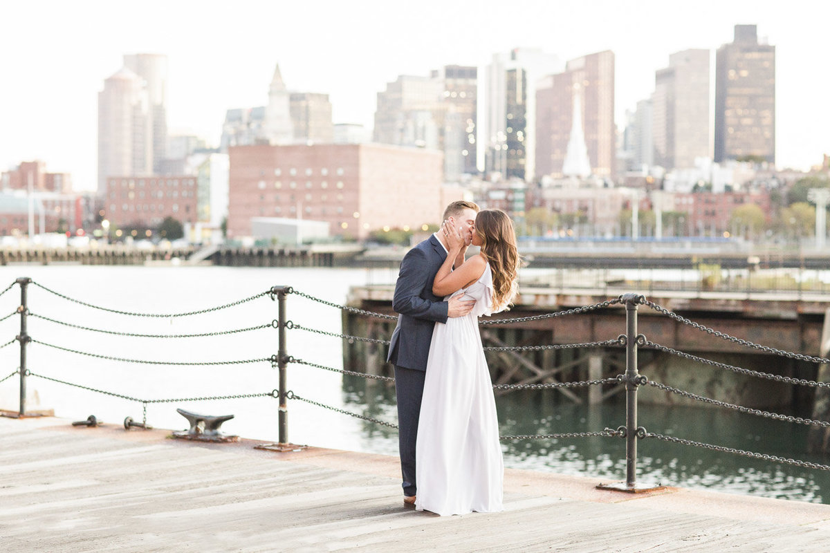 couple kissing in the Charlestown Navy Yard with Boston Skyline in the background