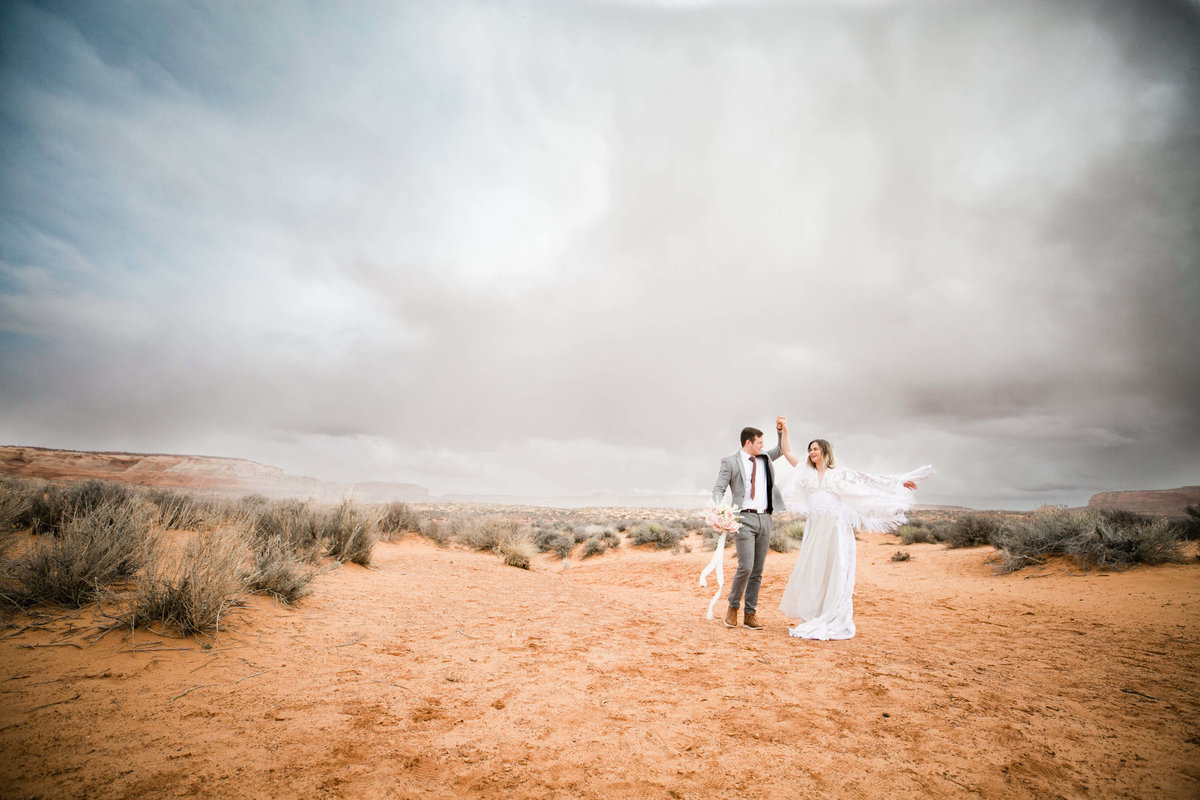 With a storm gathering behind the the eloping couple dances in the desert.
