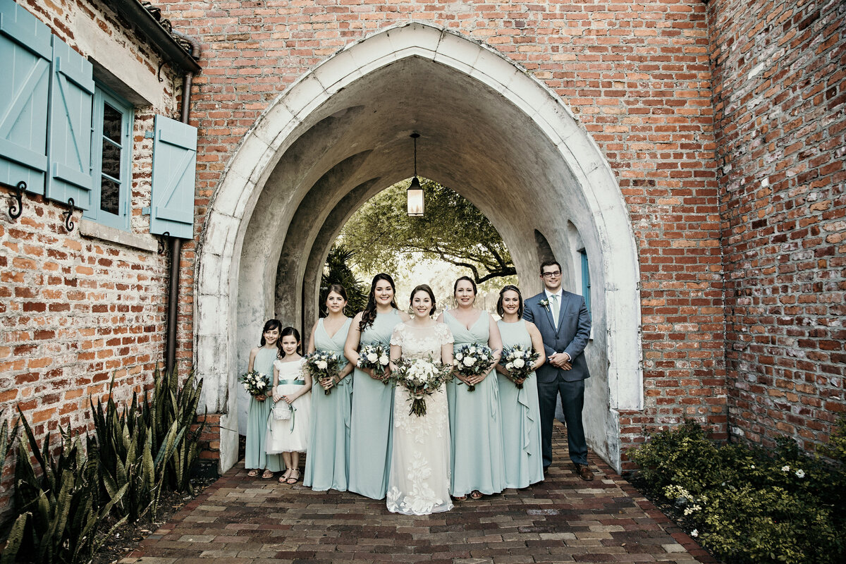 An image of a bride standing in line with her bridesmaids, flower girls, and friend as they pause in a vintage archway with old brick walls and sidewalk lined with plants by Garry & Stacy Photography Co - St Petersburg wedding photographer