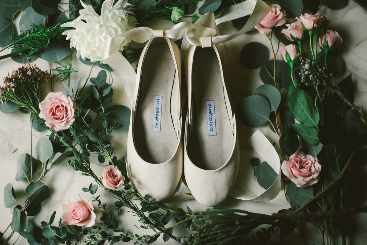 White Ribbon shoes sit in the middle of roses and greenery