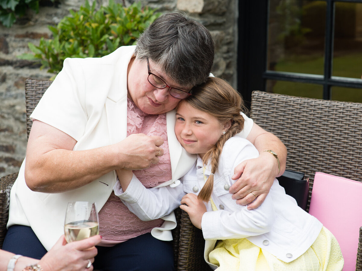 Grandmother at wedding hugging grandchild