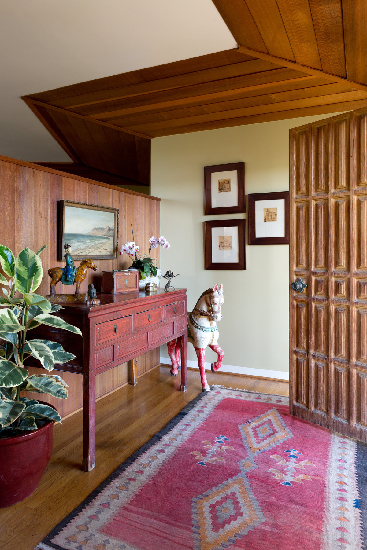 Entry with carved redwood door, vintage Navajo rug, red Chinese table, large wood horse, and rubber tree