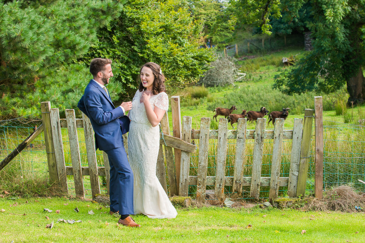 brunette bride wearing a vintage, beaded wedding dress with her groom wearing a blue suit and green, tweed tie standing in front of a wooden, picket fence with brown pygmy goats in the background