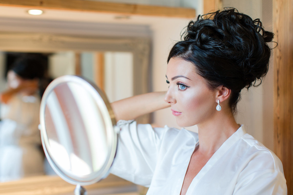 Stunning bride does her own hair and make-up for this wedding at southend barns and  looks in the mirror with the natural window light in the milking parlour bridal suite