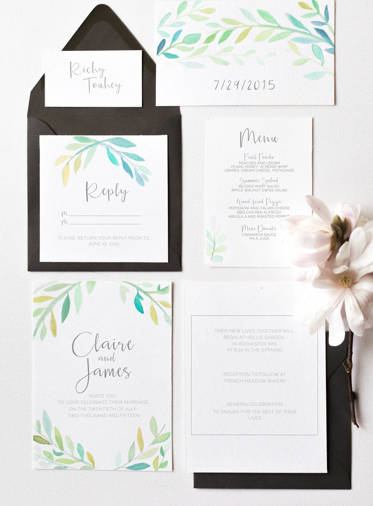simple wedding invite suite styling of watercolor and foliage black accents and magnolia flowers
