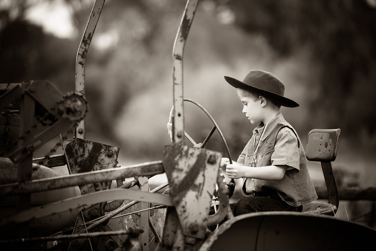 black and white picture of young boy driving antique tractor. family photographer located in billings mt