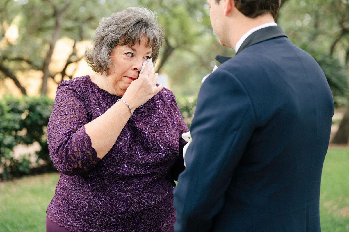Mother of groom crying in purple dress on sons wedding day
