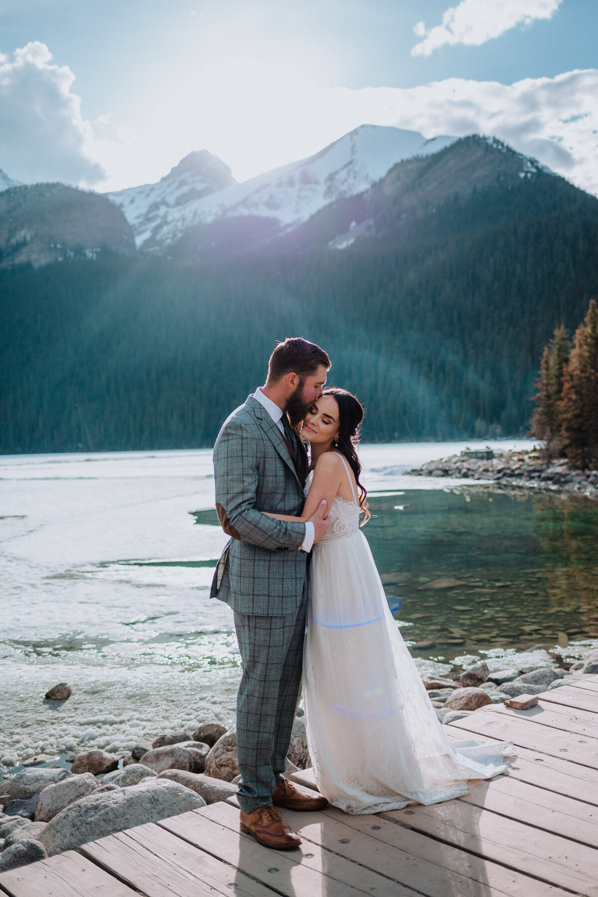 Couple snuggling in front of lake louise