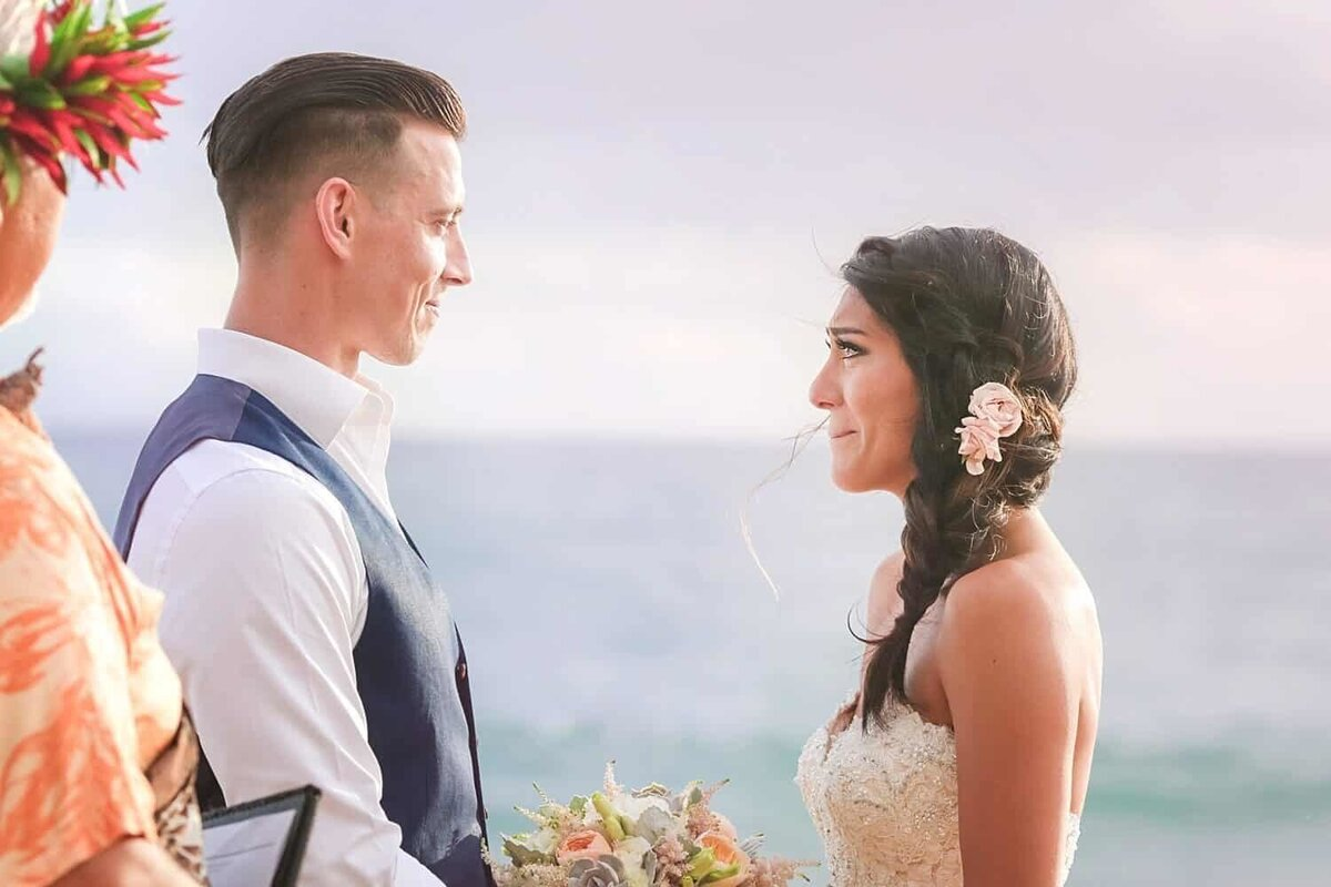 Crying bride looking up at her groom on the beach on Maui during their elopement