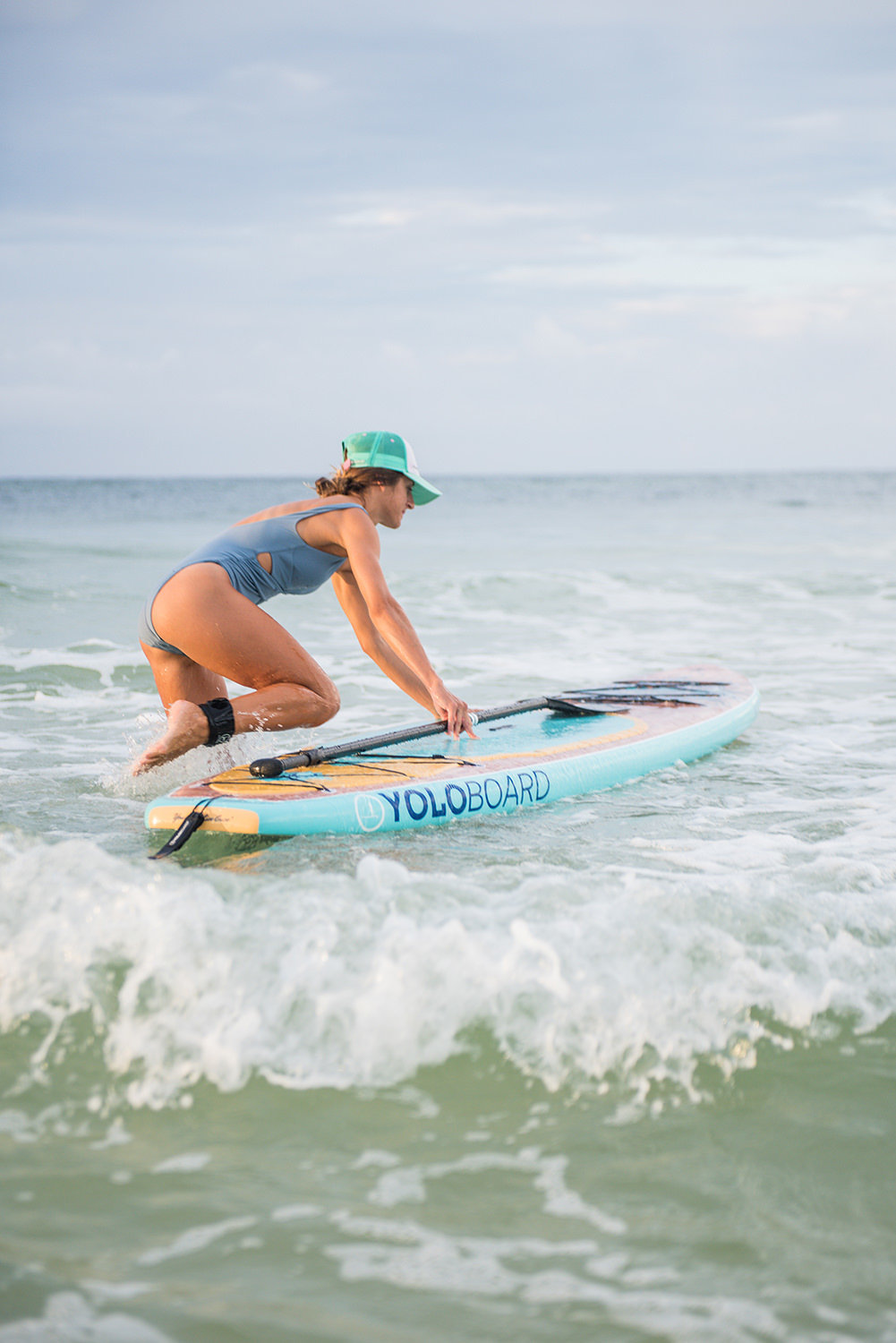 woman getting on paddle board