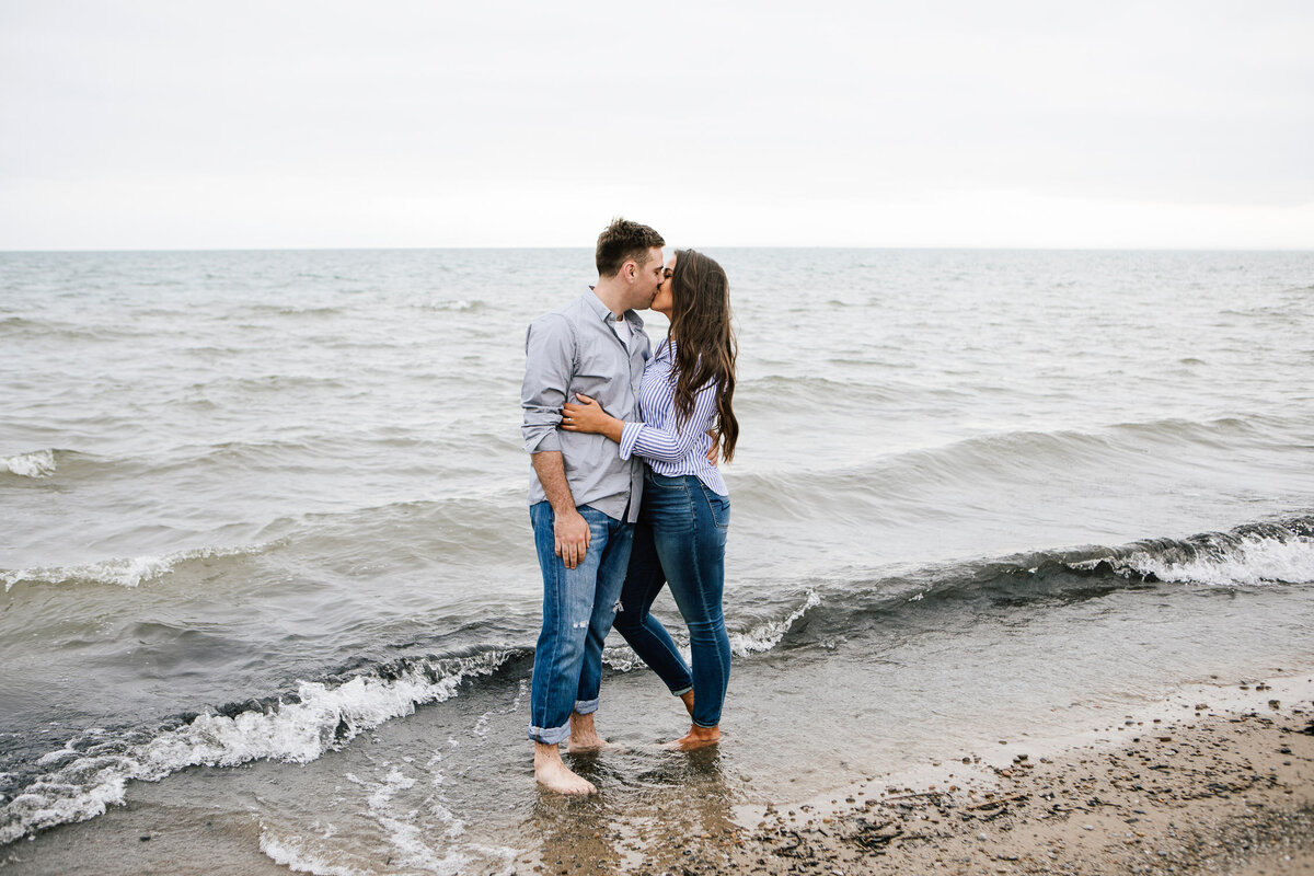 Engaged couple kissing with feet in the ocean